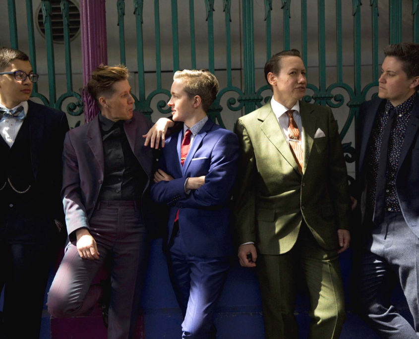 Five butches, masculine-presenting gender rebels, fabulously suited and booted. Their bodies face the camera while they talk facing each other.