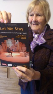 Shirley McNamara looking at a flyer of Let Me Stay