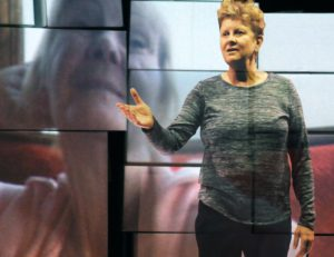 Julie McNamara in front of a projected image of Shirley McNamara in LEt Me Stay
