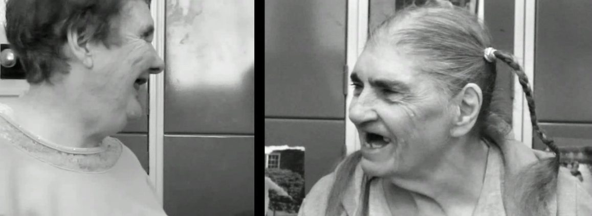Black and white photo of two elderly white women facing each other and laughing. Betty, on the left, has short brown hair and Miriam, on the right, long white hair in plaits.