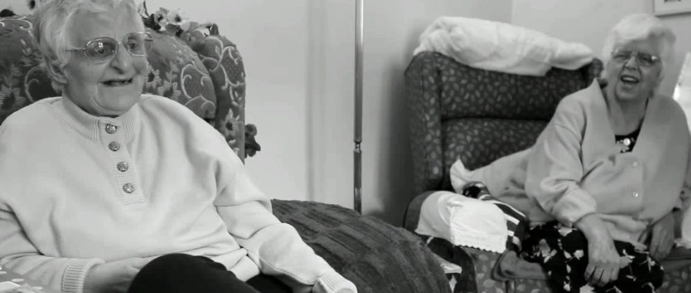 A black and white photo of former residents and survivors Mary (left) and Rosie (right). Two white elderly women in their living room. They comfortably sit on armchairs and laugh.