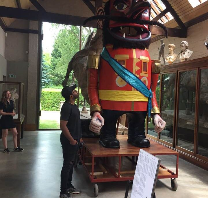 Pullen's Giant at Watts Gallery - Artists' Village, June - October 2018. Photo of a man looking at the giant puppet, which is twice as tall, in the middle of the gallery room.