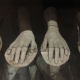 Photo description: Four plaster casts of female hands rest in an eerily lit museum display cabinet. Photo credit: JulieMc