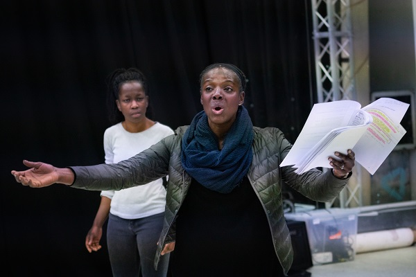 Actors in rehearsal, Fatima Niemogha and Shereener Browne who play Kem and Elaine / Elsie respectively, presenting two women of African. Shereener, in the foreground, is working script in hand and has her arms outstretched, speaking to someone else she is appealing to. Fatima, in the background, looks on, concerned.