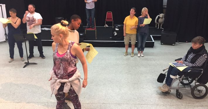 Six people standing in pairs create a triangle in a theatre rehearsal space. Another person in the background stands on a chair, on a small stage.