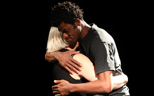 A black man and a white woman hug each other tenderly.