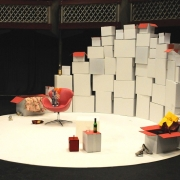 A theatre stage set in a circle. The background comprises stacks of white boxes, the ones on top are open. A '70s chair is placed at the centre of the stage, and around the stage there are two bottles of wine, high heel shoes thrown on the floor and a floral dress hanging out from one of the boxes on the floor.