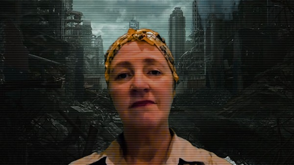 The portrait of a white woman. She firmly faces the viewer. A dystopian digital background of a destructed city. Screenshot from the online sharing via Zoom. White Pariahs - Quite Rebels Second R&D - July 2020.