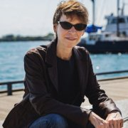 A slim white woman with short-cropped light brown hair is smiling, wearing black sunglasses, a brown leather jacket, and blue jeans, sitting outdoors in front of a harbour with a boat in the background.