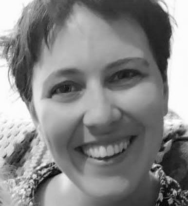 Photograph is in black and white and is of a white woman in her thirties with very short dark hair, she is smiling, the photograph is cropped to face only